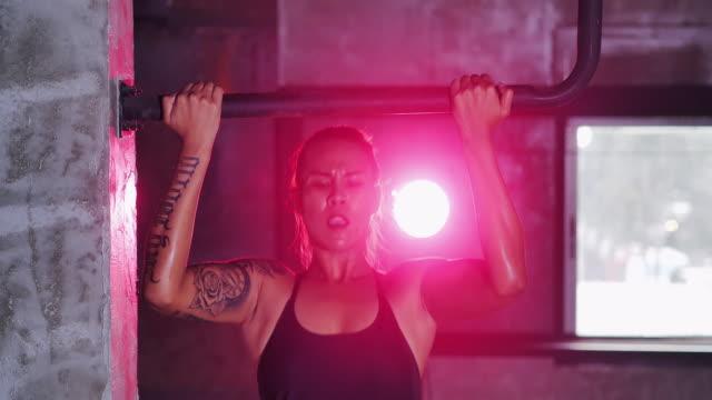 junge frauen sportliche verlegerungen pull-ups in geräumigen leichten fitnessstudio. junge sportlerinnen trainieren in bars im fitnessstudio. frauen, die sich mit pull-ups im fitnessstudio den rücken trainieren. kampfkunst - turngerät mit holm stock-videos und b-roll-filmmaterial