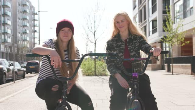 2 unga kvinnor bmx ryttare som vill kamera och leende tillsammans - mellan 30 och 40 bildbanksvideor och videomaterial från bakom kulisserna