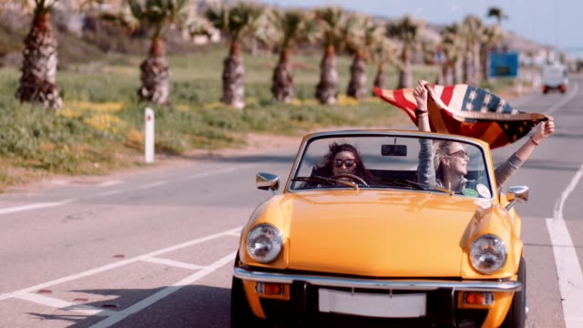 Young women celebrating with American flag in yellow convertible car Ex-pats or tourists celebrating the 4th of July by waving an American flag overseas july 4th stock videos & royalty-free footage