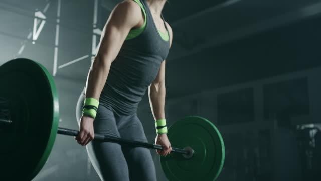 vídeos de stock e filmes b-roll de young women doing exercise with weights in gym - agachar se