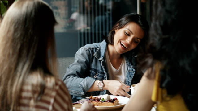 Young women eating desserts and drinking coffee in cafe talking having fun