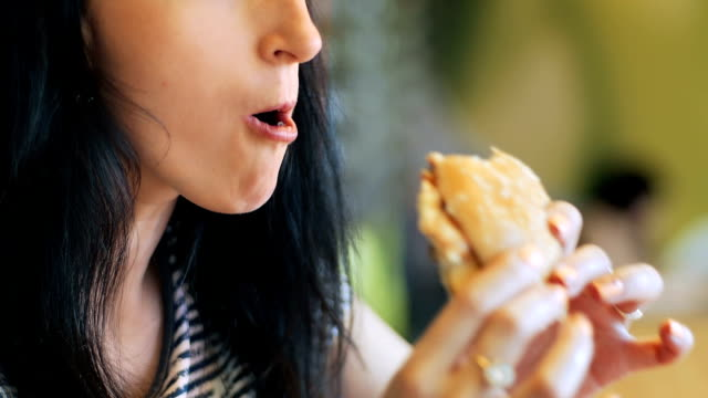 Young women eating hamburger in restaurant video