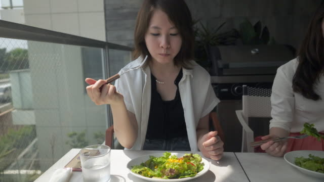 カフェのバルコニーでサラダを食べる若い女性 - サラダ点の映像素材/bロール