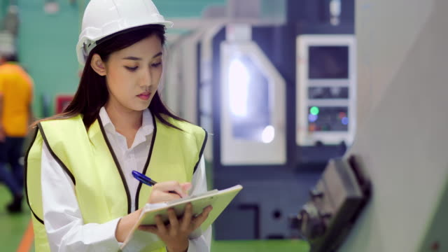 Young women engineer inspecting with tablet computer the work process of industrial CNC metal machining.Technology,Industry,Science,Innovation,Education,Industry 4.0,Women in STEM.Automation – Large Scale Industrial concept.Blue Collar Workers - vídeo