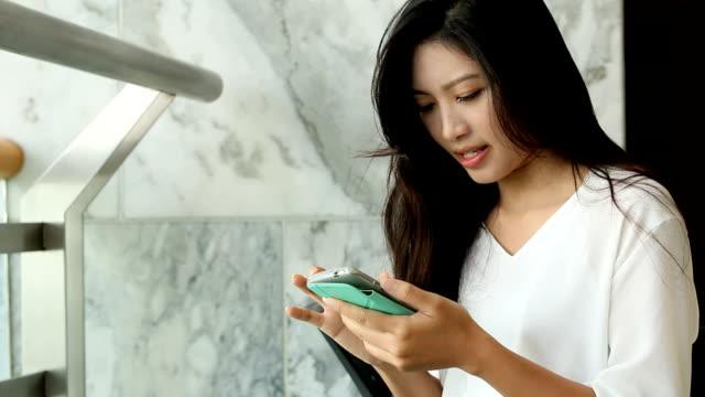 vídeos de stock e filmes b-roll de mulheres jovens desfrutar com o seu smartphone - concrete wall interior