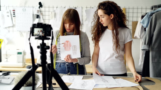 young women fashion bloggers recording video blog about ladies'clothes on camera and talking to followers in modern studio. many garment sketches are visible. - sarta video stock e b–roll