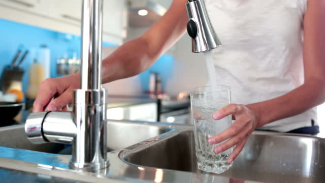 młodych kobiet napełniania kieliszek z wodą z naciśnij - tap water filmów i materiałów b-roll