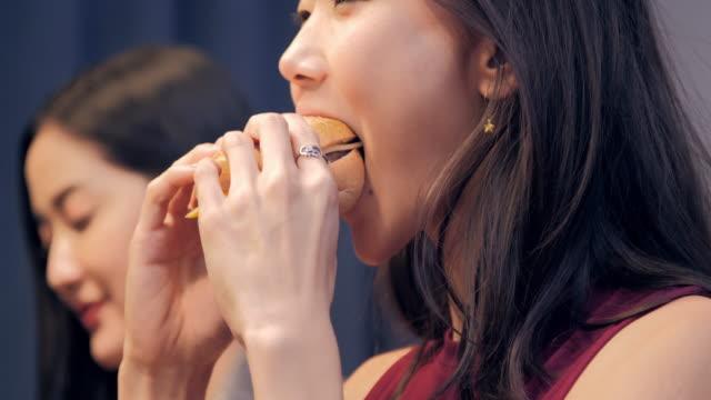junge frauen freunde spaß sitzen zusammen mit leckeren burger und getränke am abend empfängt zu hause. lifestyle: meilensteine & feiern - schnellkost stock-videos und b-roll-filmmaterial