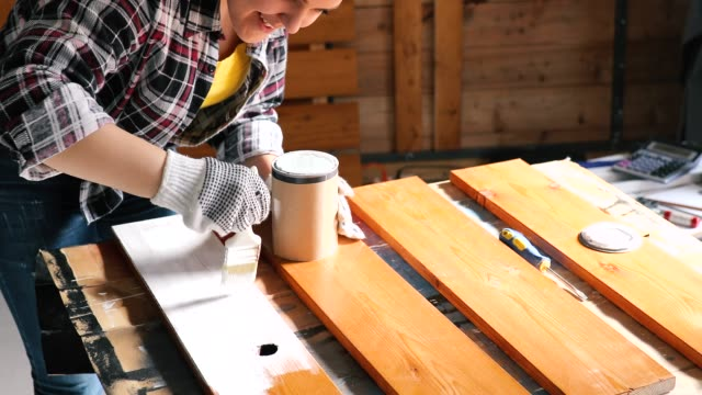 Young Women Furniture Designer Painting Plank in Garage video