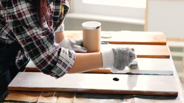 vídeos de stock e filmes b-roll de young women furniture designer painting plank in garage - bricolage