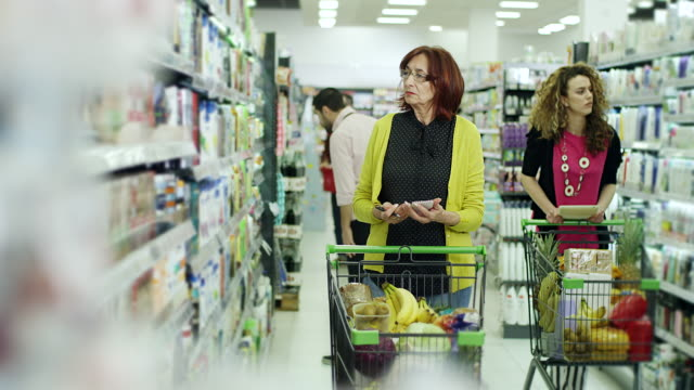 Young women helping senior women to use tablet for shopping in supermarket video