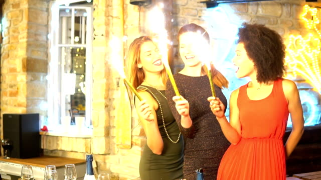 Young women holding mini fireworks video
