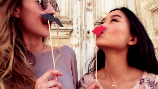 Young women holding mustaches and lips on sticks having fun video