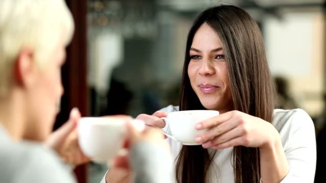 vídeos y material grabado en eventos de stock de mujeres jóvenes en la cafetería. - café bebida