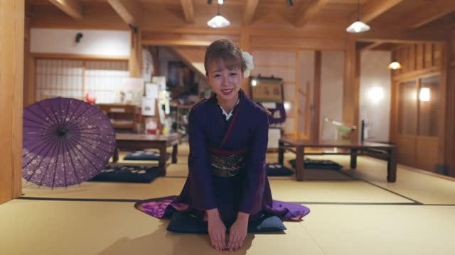 vídeos de stock, filmes e b-roll de jovens mulheres em quimono 'furisode' sentadas em saltos e curvando-se em quarto 'tatame' japonês - tradição