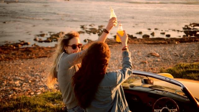 vídeos y material grabado en eventos de stock de mujeres jóvenes en coche descapotable vintage bebiendo refrescos en la playa - zumo