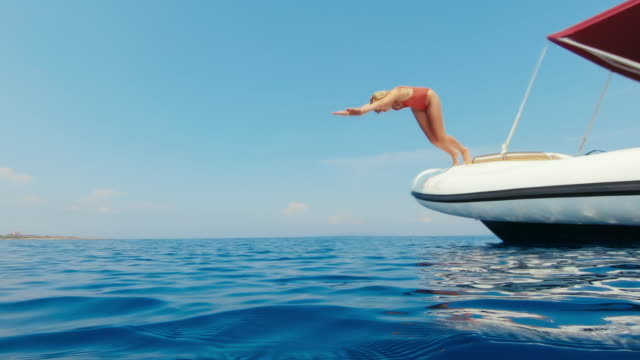 Young women jumps off the boat into the crystal clear transparent water.