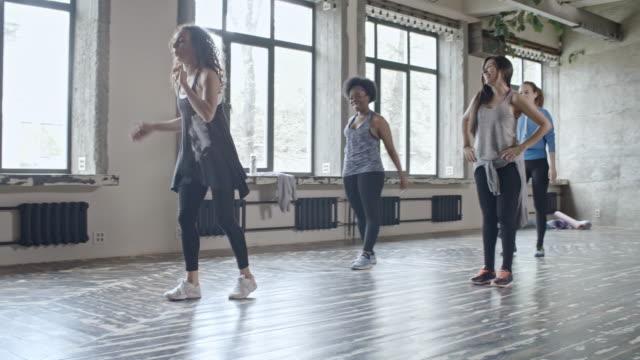 młode kobiety uczą się ruchów tanecznych w klasie - rozgrzewka filmów i materiałów b-roll