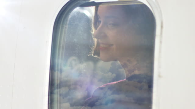 Young women looks through an airplane window and smiles during flight. video
