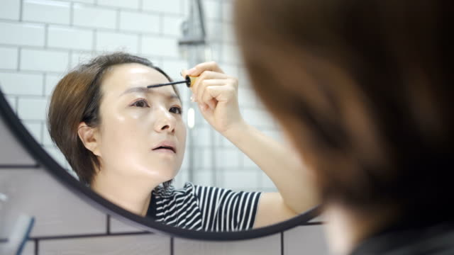 Young women make up in front of the mirror