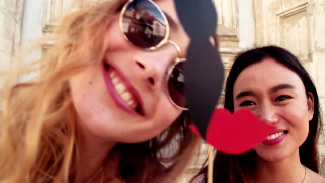 Young women making funny faces with fake mustaches and lips video
