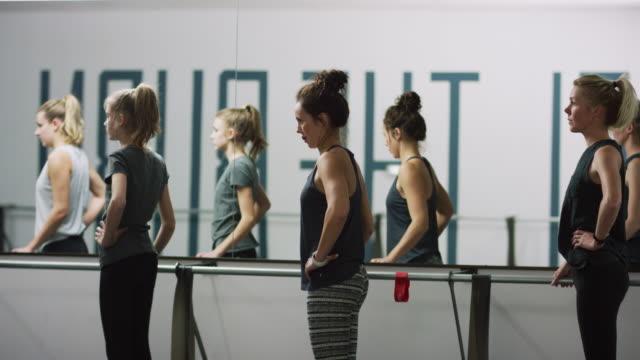 unga kvinnor i blandade åldrar står vid en balett barre på deras tiptoes i en motion studio - balettstång bildbanksvideor och videomaterial från bakom kulisserna