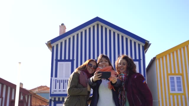 vídeos de stock e filmes b-roll de young women on a spring break taking pictures with her phone on a touristic spot on the beach. - aveiro