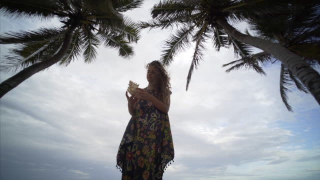 young women on seaside lonely young women uder palms with shell in hands animal shell stock videos & royalty-free footage