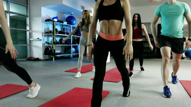 vídeos de stock e filmes b-roll de young women performs strengthening exercises for the muscles of the legs and buttocks with trainer. - agachar se