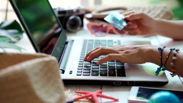 junge frauen planen sommerferienreise und suchen informationen oder buchen hotel und mit kreditkarte auf laptop, reisekonzept - eine reservierung vornehmen stock-videos und b-roll-filmmaterial