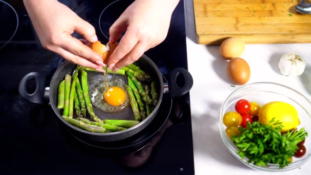 Young Women Preparing Eggs With Asparagus video