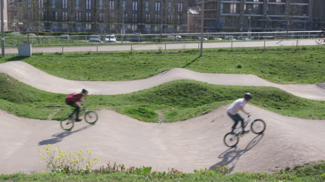 Young women racing BMX bikes on racing track