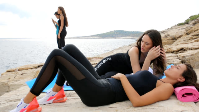Young women relaxing by the sea on the rocky beach