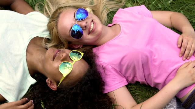 vídeos de stock, filmes e b-roll de mulheres jovens relaxando no gramado e fim de semana desfrutando, melhores amigas, sair - viagem de primeira classe