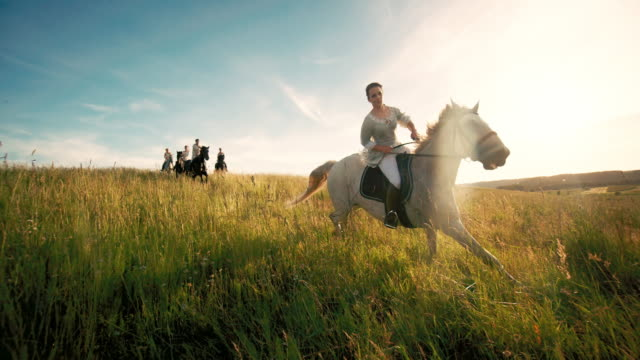 Young women riding horses on grassy field Young women riding horses on grassy field horseback riding stock videos & royalty-free footage