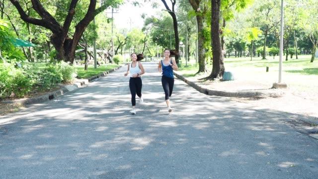 vidéos et rushes de jeunes femmes exécutant ensemble au parc - joggeuse