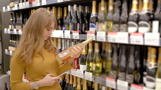 young women scanning bar code with mobile phone on wine bottle - alchol video stock e b–roll