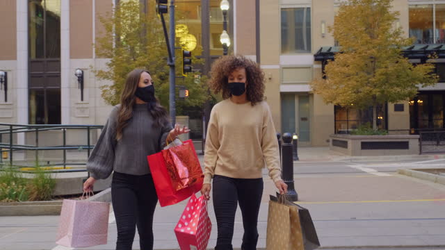 Young Women Shopping with Face Mask on for Protection Two young women, shopping in a downtown area wearing facemasks for protection. holiday stock videos & royalty-free footage