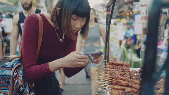 Young women taking photo of chicken and pork grill at street food