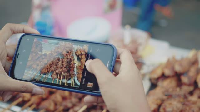vídeos de stock e filmes b-roll de young women taking photo of chicken and pork grill at street food - comida asiática