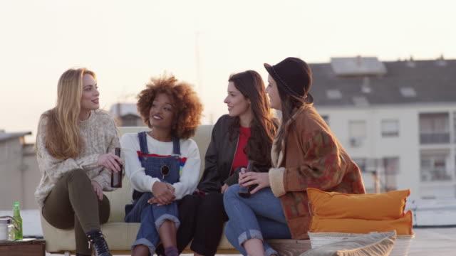 stockvideo's en b-roll-footage met jonge vrouwen te praten tijdens de partij op het dak in de zomer - vier personen