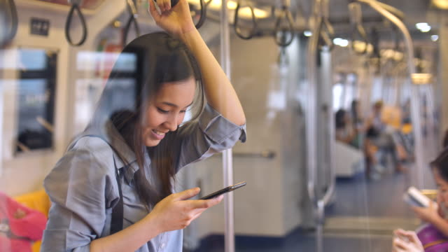 Young women typing message on the train, Slow motion video