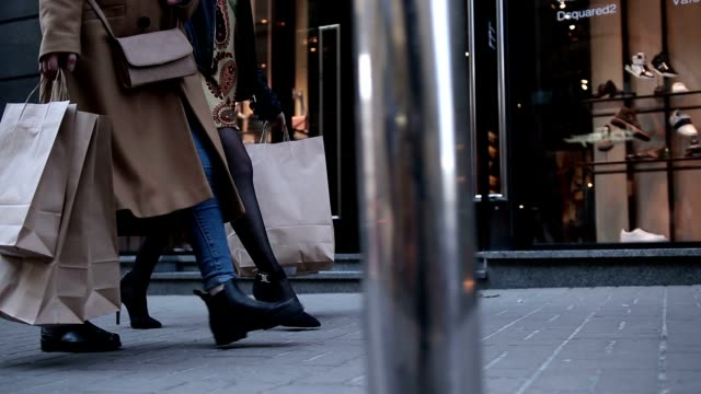 young women walking with bags after shopping - borsa della spesa video stock e b–roll