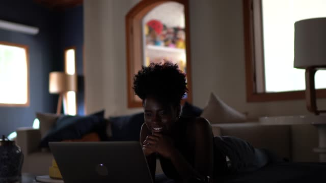 evde dizüstü bilgisayarda film izleyen genç kadınlar - dijital yerli stok videoları ve detay görüntü çekimi