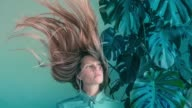 istock Young women with flying hair and monstera 1138161539