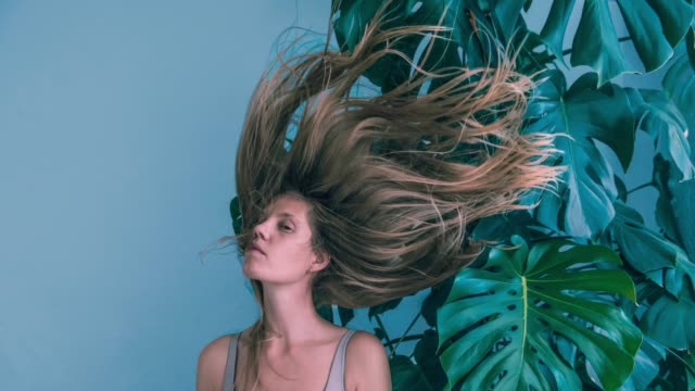 Young women with flying hair and monstera Young women with flying hair and monstera low lighting stock videos & royalty-free footage