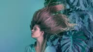 istock Young women with flying hair and monstera 1138163451
