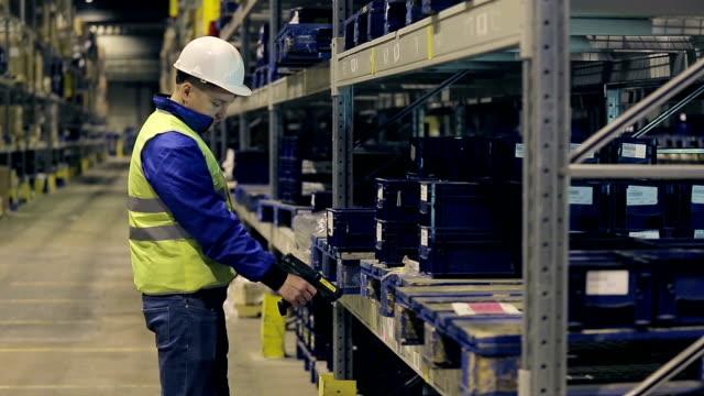 vídeos de stock e filmes b-roll de young worker checking cargo with scanner - engradado