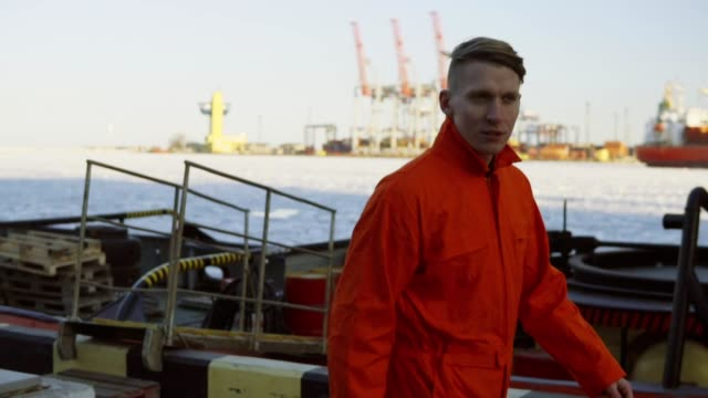 Junger Arbeiter in orange einheitliche Spaziergang durch den Hafen am Meer während seiner Pause. Freizeit – Video