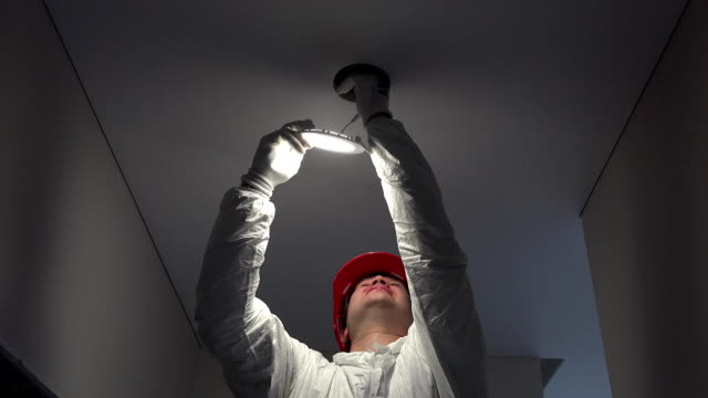 young worker man installing led lights on ceiling hole video
